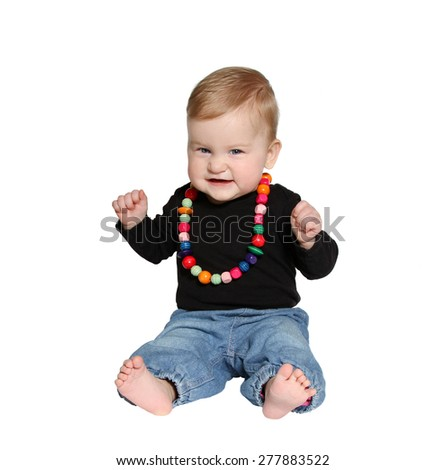 smiling baby sits with colorful handmade wooden necklaces looking at camera on white background - stock photo