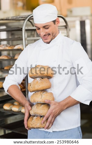 Smiling baker holding fresh loaves in the kitchen of the bakery - stock photo