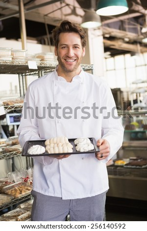 Smiling baker holding meringue tray at the bakery - stock photo