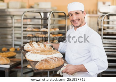 Smiling baker holding tray of bread in the kitchen of the bakery - stock photo