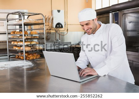 Smiling baker using laptop on worktop in the kitchen of the bakery - stock photo