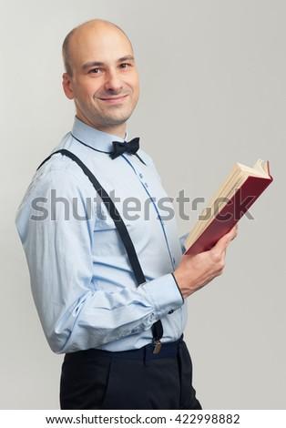 smiling bald man reading a book. Studio shot - stock photo