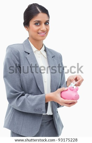 Smiling bank assistant putting money into piggy bank against a white background
