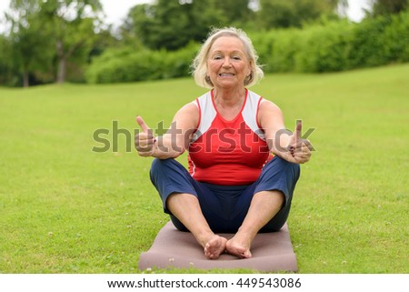 Smiling barefoot senior woman sitting on yoga mat with thumbs up outdoors in park with wide open field of green turf grass and copy space - stock photo