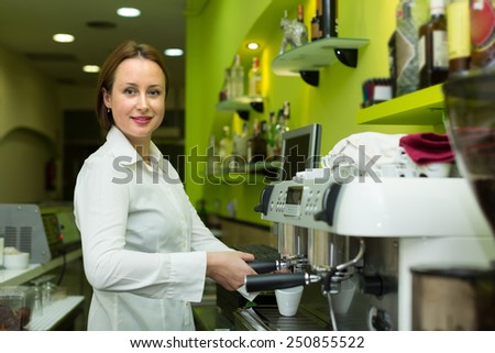Smiling barista girl making cup of coffee in cafe - stock photo