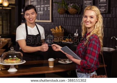 Smiling barista taking credit card from customer at the coffee shop