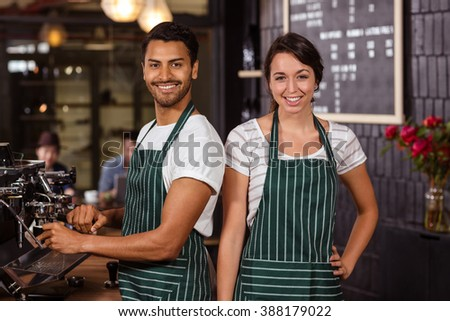 Smiling baristas working in the bar