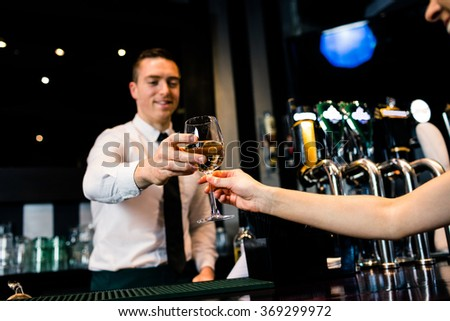 Smiling barman giving glass of white wine to client in a bar - stock photo
