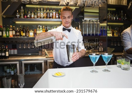Smiling bartender preparing a drink at bar counter in a bar - stock photo