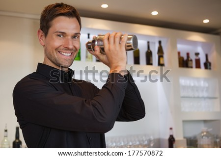 Smiling bartender shaking cocktail at the bar - stock photo