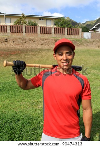 Smiling baseball player poses in a park field - stock photo