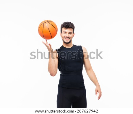 Smiling basketball player spinning ball on his finger isolated on a white background and looking at camera - stock photo