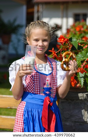 Smiling  bavarian girl eating  pretzel and drinking milk  on the farm in Germany . - stock photo
