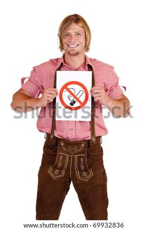 Smiling Bavarian man in lederhose holds non-smoking-rule sign. Isolated on white background. - stock photo