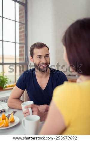 Smiling bearded man enjoying breakfast smiling at his wife as he drinks a mug of coffee while seated at the table, over the shoulder view - stock photo