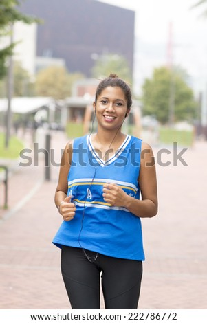 Smiling beautiful athletic woman running in the street.