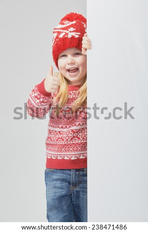 Smiling beautiful blond girl in a red winter cap and sweater with white space for text or advertisement - stock photo