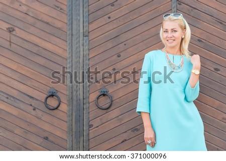 Smiling beautiful blonde woman looking at camera - stock photo