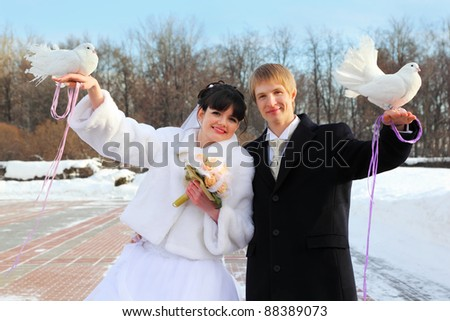 smiling beautiful bride and groom hold white doves at winter outdoors - stock photo