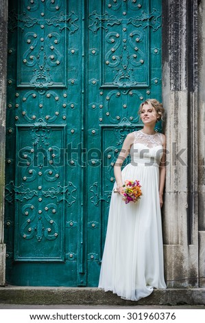 Smiling beautiful bride on her wedding day with a big bouquet walking in old town - stock photo