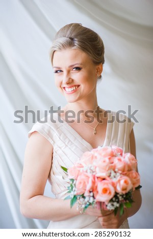 Smiling beautiful bride on your wedding day with a big bouquet