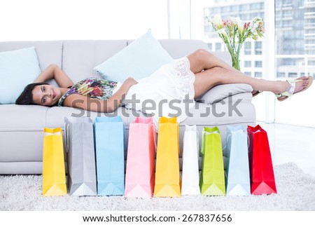 Smiling beautiful brunette lying on the couch with shopping bags around her in the living room - stock photo