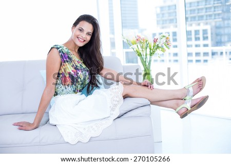 Smiling beautiful brunette sitting on the couch and looking at camera in the living room - stock photo