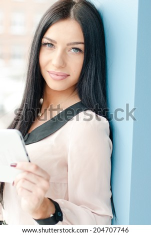 Smiling beautiful brunette young business woman using tablet PC computer & looking at camera while standing relaxed near window at her office on blue wall copy space background closeup portrait image - stock photo