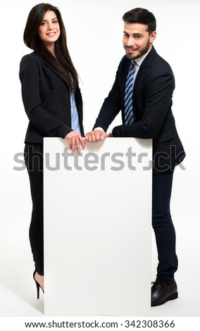 Smiling beautiful business people showing a white board - stock photo