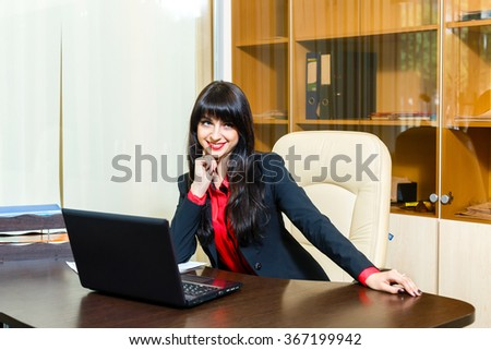 Smiling beautiful businesswomen sitting at the table in the office with paperwork and laptop