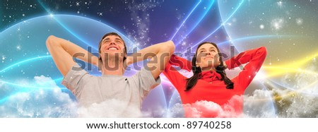 Smiling beautiful couple sitting on a sofa at their apartment and dreaming about something - stock photo