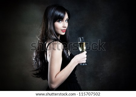 smiling beautiful elegant young woman with glass of champagne studio shot - stock photo