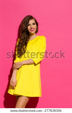 Smiling Beautiful Girl Against Pink Wall. Smiling young woman in yellow mini dress posing against pink background. Three quarter length studio shot. - stock photo