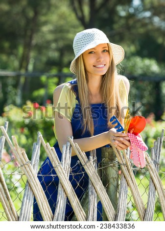 Smiling beautiful girl in hat gardening with roses in sunny day
