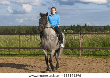 Smiling beautiful girl on a horse - stock photo