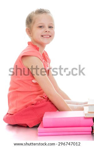 Smiling beautiful girl schoolgirl in a pink dress sitting on the floor next to her are textbooks notebooks , the girl is preparing to do her homework, she makes good grades in school-Isolated on white - stock photo