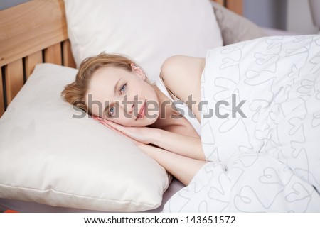 Smiling beautiful girl tries to fall asleep in bed with white linen - stock photo