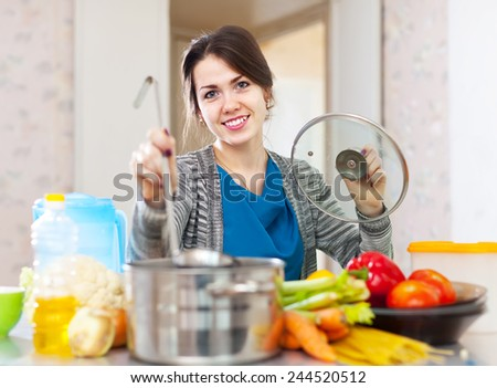 Smiling beautiful housewife cooking with ladle at her kitchen  at home