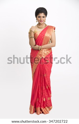 Smiling beautiful Indian young girl posing in traditional Indian saree on white background.  - stock photo