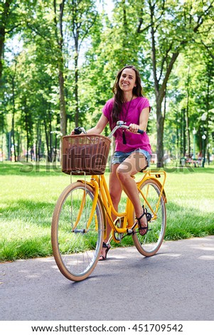 Smiling beautiful lady is riding a bright yellow bike in recreational area in summer  - stock photo
