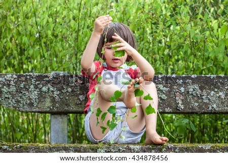 smiling beautiful little child playing with hands and legs with foliage and long stems of ivy to learn nature in garden in summertime