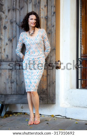smiling beautiful middle-aged woman near ancient doors in the old town - stock photo