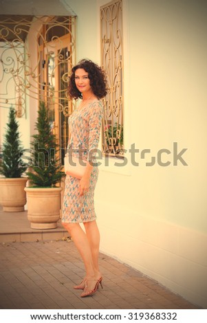 smiling beautiful middle-aged woman with beige handbag on ancient street of little town. copy space. instagram image filter retro style - stock photo