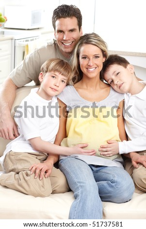 Smiling beautiful pregnant mother and family  at home - stock photo