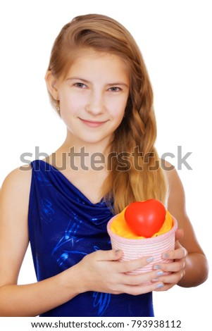 Smiling beautiful teen girl with a gift and a symbolic red heart