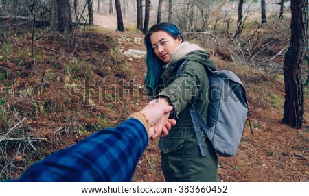 Smiling beautiful traveler young woman with backpack holding man's hand and leading him in the pine forest outdoor. Point of view shot - stock photo