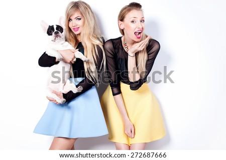 Smiling beautiful two girls posing with pug dog. Summer photo. Fashionable style. - stock photo