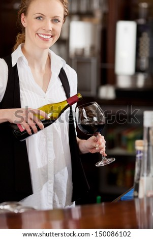 Smiling beautiful waitress pouring a glass of red wine into an elegant long stemmed wineglass in a restaurant or club