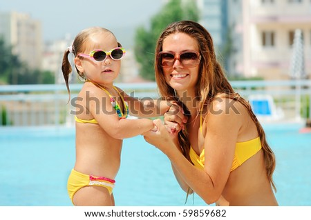 Smiling beautiful woman and her little cute daughter in sunglasses have a fun in pool outdoor - stock photo