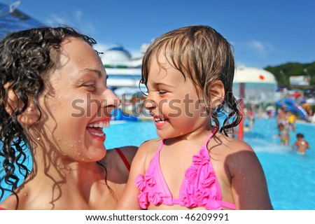 Smiling beautiful woman and little girl bathing in pool of an entertaining complex, Looking against each other